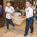 Julianna Zuniga and Angel Arjon carry a basket with CRS Rice Bowls in procession during Mass at St. Willebrord Church in Green Bay April 26. The rice bowls held donations that members of Amigos de Jesus, the St. Willebrord youth group, raised during Lent. (Sam Lucero | The Compass)