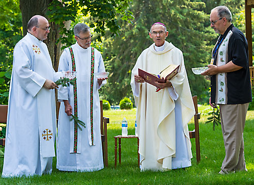 Auxiliary Bishop Emeritus Robert Morneau leads a blessing of water and sprinkling rite at Jesuit Retreat House in Oshkosh July 11. He is assisted by Jesuit Fr. Chris Manahan, left, retreat house director, Jesuit Fr. John Schwantes, former director, and Deacon John Ingala. (Sam Lucero | The Compass)