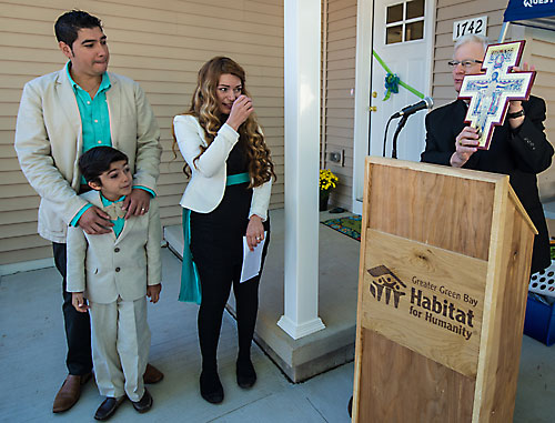 Bishop David Ricken presents a San Damiano cross to Alberto Castro and Elizabeth Gomez during the dedication of their home, which they helped build through Habitat for Humanity of Green Bay. The house was built in honor of Pope Francis. Bishop Ricken explained that diocesan seminarians in Rome had the cross blessed by Pope Francis. Gomez was moved to tears by the gesture. As part of the dedication, Bishop Ricken blessed each room in the Castro-Gomez home with holy water. (Sam Lucero | The Compass)