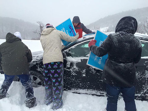 Students from the Diocese of Green Bay use pro-life posters to clean snow from a car's windshield. A major snowstorm stranded the group on buses near Somerset, Penn., since around 10 p.m. Jan. 22. (Submitted Photo | The Compass)