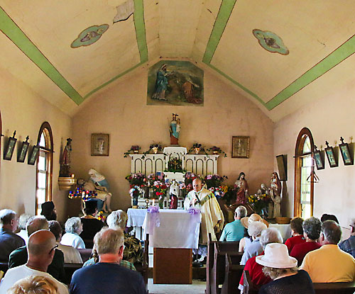 Salvatorian Fr. Patrick Nelson celebrates Mass on the Fourth of July at Lax Chapel, south of St. Nazianz in rural Manitowoc County. On the altar and behind the altar stand two statues of Our Lady of Loucim, the only two known to exist in the United States, according to Lee Thompson of Milwaukee. (Benjamin Wideman | For The Compass)