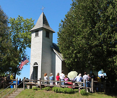 Churchgoers who couldn't fit inside the Lax Chapel for a Fourth of July Mass stand outside the chapel and listen via a speaker system. About 40 of the roughly 150 people who attended the Mass could fit inside the chapel, which was built by Frank Lax in 1875. (Benjamin Wideman | For The Compass)