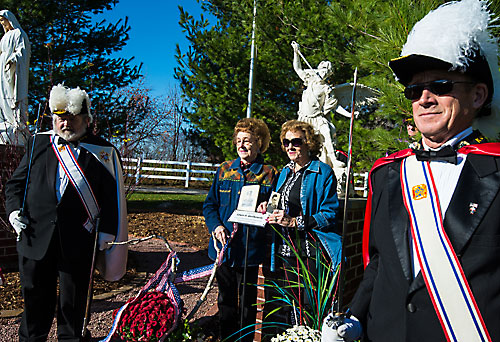 Knights of Columbus honor guard members flank the sisters of Edwin Gerlikowski, Ellie and Mary Watermolen, who hold pictures of their late brother in front of the St. Michael the Archangel statue dedicated in his memory Nov. 8. (Sam Lucero   The Compass)